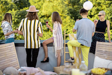 Young Stylish People Enjoy View On Nature From The Rooftop Terrace, Hanging Out At Party Outdoors. View From The Backside