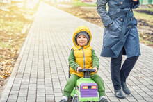 Happy Little Boy Kid In Bright Yellow Vest Pushes Ride-on Toy Walking With Mother Wearing Grey Coat Along Road In Autumn Park
