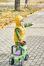 Sweet Little Boy In Bright Yellow Vest Points With Finger Standing Near Ride-on Toy Walking On Paved Road In Sunny Autumn Park