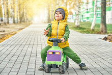 Happy Little Boy Kid In Bright Yellow Vest Pushes Ride-on Toy While Walking On Paved Road In Sunny Autumn Park
