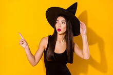 Photo Of Frightened Witch Lady Point Empty Space Wear Black Dress Cap Isolated On Yellow Color Background