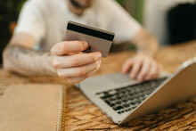 Crop Man Making Payment With Plastic Card During Online Shopping