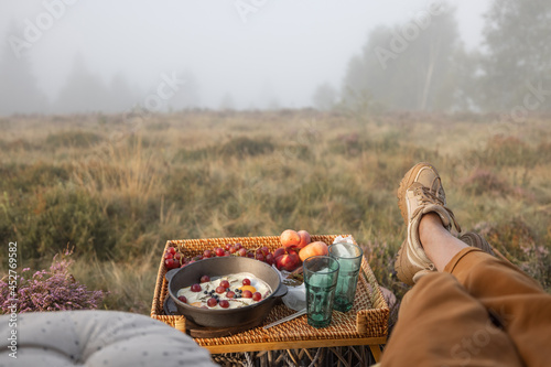 Carta da parati Woman having a picnic and enjoying great view on nature in foggy weather, sittin