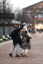Joyful Young Couple Travel On Christmas Enjoy Walking Outdoors Spinning And Dancing In Empty Old Town. Happy Lovers Have Fun Outside On Street In Snow Dressed In Warm Clothes During Vacation Together
