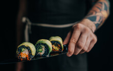 Unrecognizable Man Chef With A Tattoo On His Arm Holds Sushi Rolls On A Knife.