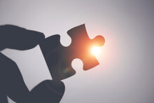 Close Up Hand Holding Jigsaw Puzzle Paper With Rays Light.