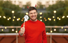 Holiday And People Concept - Happy Smiling Man In Halloween Costume Of Devil With Party Accessory Over Garland Lights At Roof Top Party Background