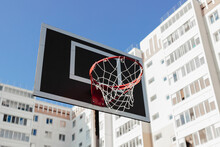 Basketball Hoop Outside In Front Of Blue Sky. Basket Red Ring With Mesh On Black Backboard. Team Game. Summer Activity, Healthy Lifestyle, Workout, Sport, Fitness. Having Fun Outdoors. Playground