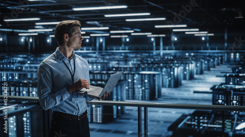 Data Center Specialist Engineer Using Laptop Computer. Server Farm Cloud Computing Facility with Male Maintenance Administrator Working. Data Protection Network for Cyber Security.