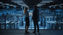 Data Center Male It Specialist And Female E-Commerce Manager Talk, Use Laptop. Big Server Farm Cloud Computing Facility With Information Technology Professionals Working.