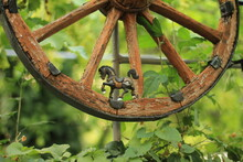 A Prancing Toy Horse And An Antique Wheel