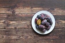 Fresh Plums In A Vintage Bowl On An Old Wooden Table. Flat Layot, Copy Space