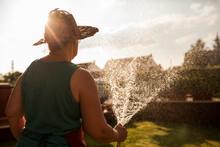 Woman Gardener Watering Her Garden With Hose