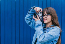 Woman Taking Photo On Retro Camera Against Blue Wall