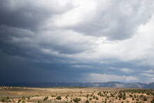 Dramatic Sky With Storm Clouds And Distant Rain Falling Down   Dark Clouds Over Plains And Mountains In The Distance, On A Sunny Day, With Heavy Rain Falling Down