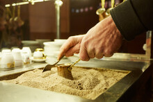 Close Up Hands Of A Man Cooking Turkish Coffee On Hot Golden Sand.