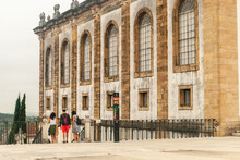 Tourists Near The Entrance Of The Joanina Library At The University Of Coimbra Square Going Down The Stairs Cloudy Day - Portugal