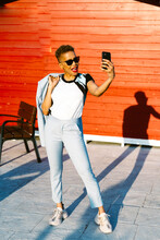 Stylish Black Woman In Sunglasses Speaking On Smartphone On Street