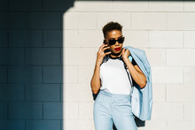 Trendy Ethnic Woman In Sunglasses Talking On Smartphone On Street
