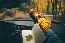 Woman With Yellow Scarf And Legs In Casual Brown Boots Stuck Out Of Car Window, Keep Yellow Maple Leaves In Paper Diary While Traveling By Car Along Rural Road Across Picturesque Autumn Forest Closeup