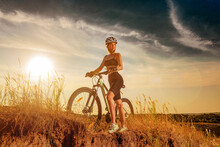 Biker-girl At The Sunset With Mountain Bike. Woman With Bicycle At Sunrise On Trail.