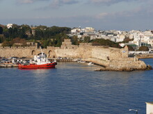 Tugboat In The Embaria Port Of Rhodes Town, Rhodes, Greece, On The Headland Of The Nailac Tower, On The Right In The Picture The Nea Agora Market Hall