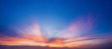Bright Blue Sky With Purple Clouds At Sunset.