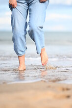 Bare Feet Walking On The Beach