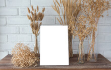 Background Composition With Many Different Dried Flowers  In A Glass Bottle On A Wooden Table, Mockup White Picture Transparent Photo Frame, Copy Space For Product Display.
