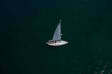 Large White Boat With Sails On Blue Water Aerial View. Lonely Sailboat On The Water Top View. Boat With Sails, Blue Water With High Altitude. Sailboat On Lake Garda, Italy.