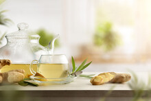 Cup With Ginger Drink On Bench With Teapot In Kitchen