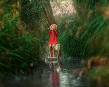 A Little Girl In A Straw Hat And Red Dress Stands Sitting On A Ladder In The River With A Fishing Rod In His Hands. Child Fishing On A Summer Day. Adventure Day Trip Into Wild Nature