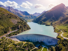 Water Dam And Reservoir Lake In Swiss Alps Generating Hydroelectricity. Aerial View Of Arch Dam Between Mountains. Hydropower Green Energy For Sustainable Development Against Global Warming. Zero CO2