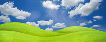 Panorama Landscape Of Green Grass Field On A Hill With Beautiful Blue Sky With Clouds. Ecology And Natural Background Concept.