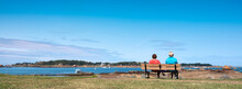 Couple On Bench Looks At Ferry To Ile De Brehat In French Brittany