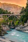 Edith Cavell Bridge in New Zealand with beautiful sunset and rapid river beneath.