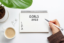 Female Hand Writes In Notepad Of Goals 2022 On White Background, Top View
