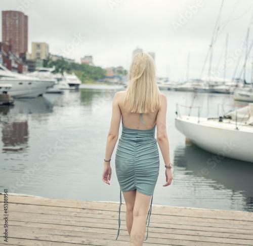 Woman in blue dress enjoys sea on the pier.
