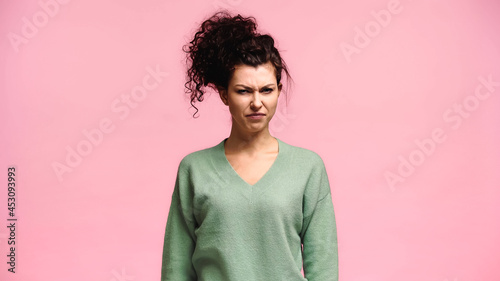 Fotografia displeased woman frowning while looking at camera isolated on pink