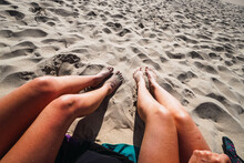 Two Pair Of Women's Legs In The Sand On The Beach