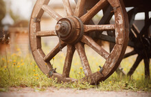 Wooden Homemade Wheels Of An Old Vintage Cart That Stands On A Rural Road Near Yellow Wildflowers And A Wooden Church On A Summer Day. Agricultural Industry.