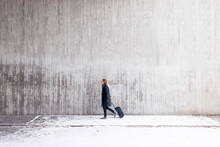 Young Man With Suitcase Walking Along Wall In Winter