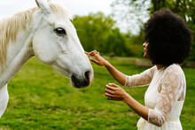 Black Woman Caressing Gray Horse In Countryside