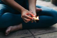 Crop Woman Lighting Incense Stick During Meditation On Dock