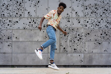 Energetic Black Man Jumping Against Creative Wall With Holes