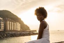 Serene Black Woman Sitting On Embankment Near Sea In Evening