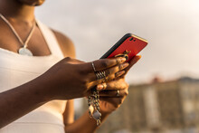 Anonymous Black Woman Sending A Message On Smartphone Near Sea In Sunset