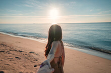 Asian Woman Holding Hands With Boyfriend Walking On The Beach With Sunshine At Morning On Vacation