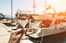 Glass Of Wine In Hand. A Glass Of White Wine Against The Backdrop Of The Mediterranean Sea And The Port With Yachts In A Tourist Town In The Summer Under Sunlight. Summer, Travel, Lifestyle