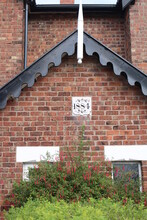 Close Up Victorian Red Brick House Built In 1884 With Date Plaque And Decorative Wooden Roof Trim And Finial
